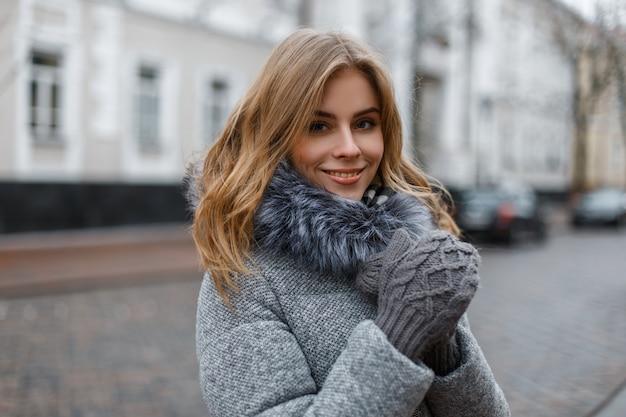 Attraente giovane donna bionda con un bel sorriso in un elegante capospalla invernale caldo in guanti lavorati a maglia si trova in città su edifici d'epoca. ragazza alla moda felice.