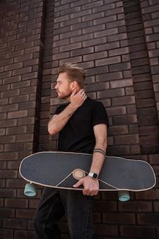 Attraente giovane biondo longboarder skater nel profilo si erge contro il muro di mattoni della città tiene longboard in legno guardando seriamente a distanza indossa denim nero vestito smart watch accessori argento.