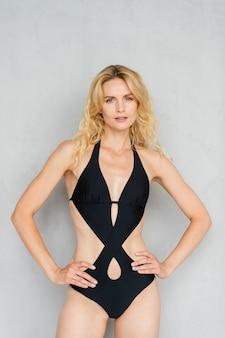 Attraente giovane modella bionda in costume da bagno nero in posa in studio