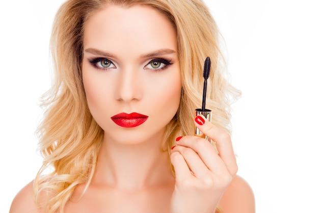 Attraente giovane bionda con labbra rosse, tenendo il pennello di mascara