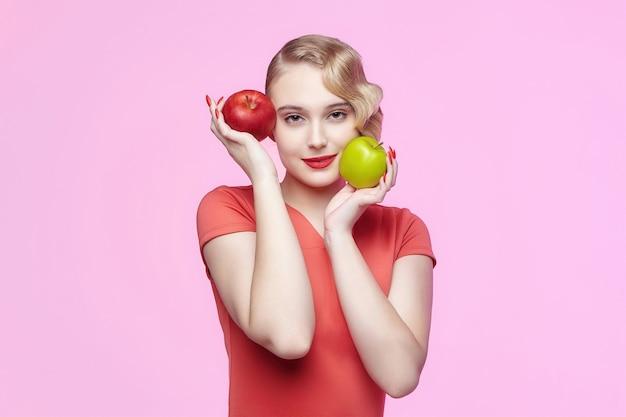Attraente giovane bionda con un'acconciatura retrò tiene una mela rossa e verde davanti al viso