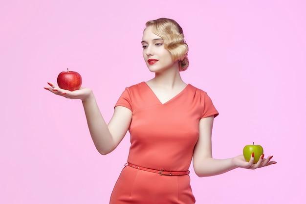 Attraente giovane bionda con un'acconciatura retrò tiene una mela rossa e verde nelle sue mani. servizio fotografico su sfondo rosa