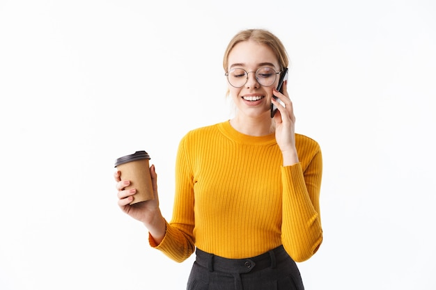 Attraente giovane donna bionda che indossa un maglione in piedi isolato su un muro bianco, parlando al telefono cellulare, tenendo una tazza di caffè da asporto