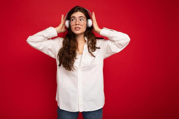 Attraente giovane donna bruna persona che indossa una camicia bianca e occhiali ottici isolati su red