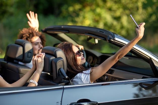 Attraente giovane donna bruna in occhiali da sole si siede con gli amici in una cabriolet nera sorride e fa un selfie in una giornata di sole. .