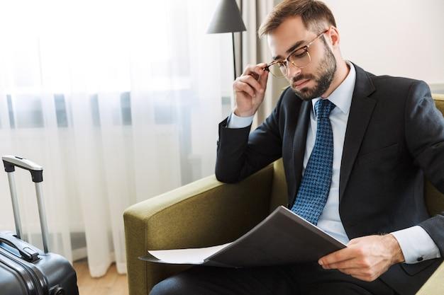Attraente giovane uomo d'affari che indossa un abito seduto su una sedia nella camera d'albergo, lavorando con documenti