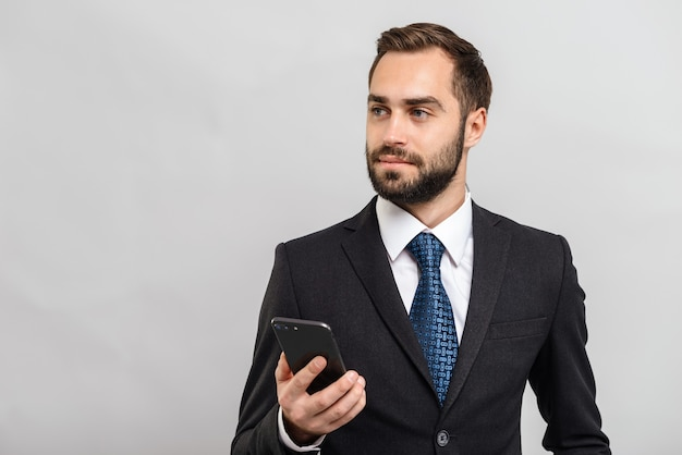 Attraente giovane uomo d'affari che indossa un abito in piedi isolato su un muro grigio, con in mano un telefono cellulare