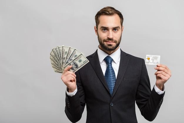 Attraente giovane uomo d'affari che indossa un abito in piedi isolato su un muro grigio, mostrando banconote in denaro e carta di credito in plastica