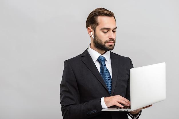Attraente giovane uomo d'affari che indossa un abito in piedi isolato su un muro grigio, utilizzando un computer portatile