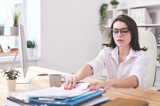 Attraente giovane imprenditrice seduto alla scrivania in ufficio e trovare documenti in pila