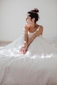 Attraente giovane donna caucasica che si rilassa bene a letto durante la mattinata la signora gode di lenzuola fresche e morbide e di un materasso in camera da letto