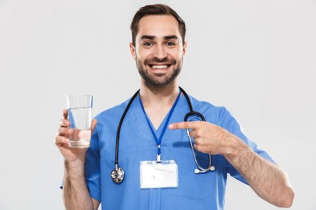 Attraente giovane medico maschio allegro che indossa l'unifrom in piedi isolato su un muro bianco, mostrando un bicchiere d'acqua
