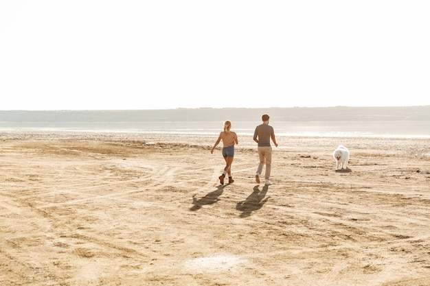 Attraente giovane coppia che gioca con il loro cane sulla spiaggia soleggiata
