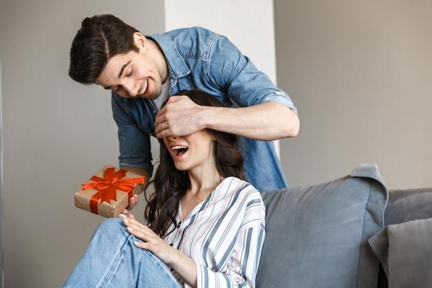 Attraente giovane coppia che si rilassa su un divano a casa, festeggia, fa regali, copre gli occhi