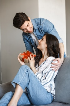 Attraente giovane coppia che si rilassa su un divano a casa, festeggia, fa regali