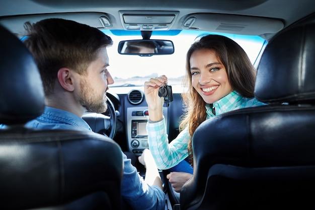 Attraente giovane coppia seduta nella nuova automobile e guardando la fotocamera e sorridente, l'acquisto di una nuova auto, tenendo le chiavi.