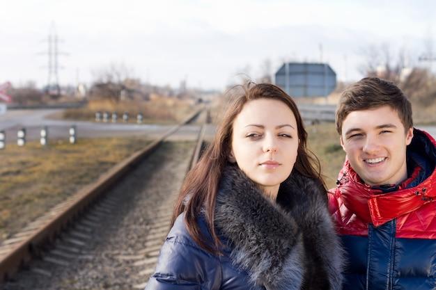 Attraente giovane coppia in caldo abbigliamento trapuntato in piedi insieme in attesa lungo un binario ferroviario per l'arrivo del treno train