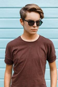 Uomo attraente giovane hipster alla moda in occhiali da sole neri alla moda in maglietta marrone alla moda pone in una città vicino a un edificio in legno blu in una giornata estiva