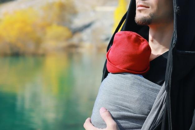 Attraente giovane padre con il suo bambino neonato nell'imbracatura all'aperto l'uomo sta portando il suo bambino e viaggia