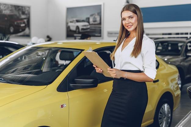 Rivenditore di auto femminile giovane attraente in piedi in showroom