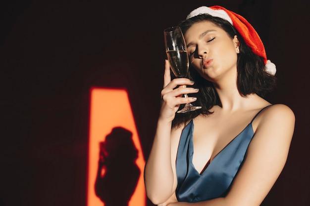 Attraente giovane donna in cappello di natale tenendo gli occhi chiusi e baci aria mentre si tiene un bicchiere di champagne e baci aria mentre si trova in una stanza buia