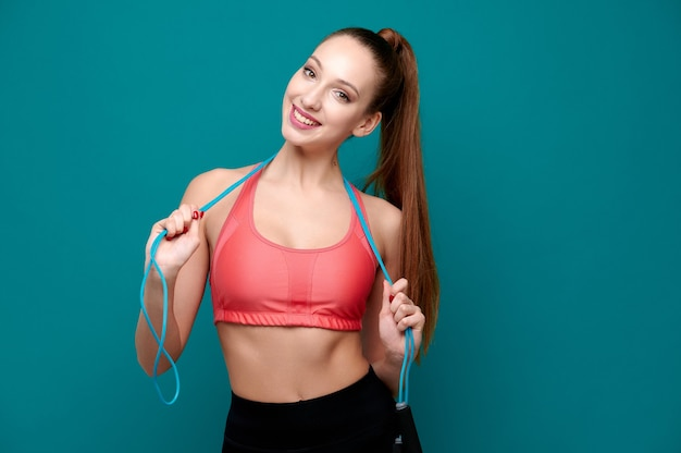 Attraente giovane allenatore di fitness femminile in abbigliamento sportivo con corda per saltare su sfondo verde isolato