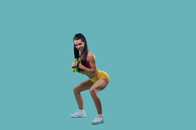 Istruttore di fitness femminile giovane attraente che esegue squat con manubri