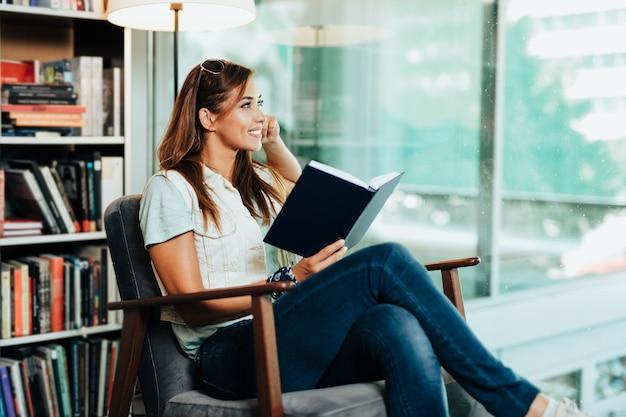 Attraente giovane studentessa che sceglie libri in libreria.