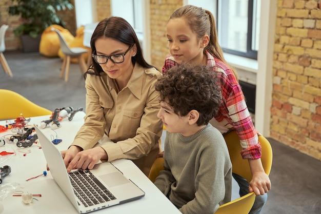 Attraente giovane insegnante con gli occhiali che mostra video di robotica scientifica ai bambini che usano