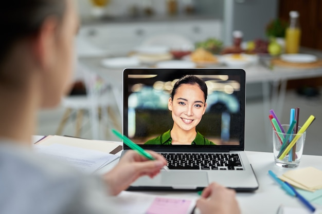 Attraente giovane insegnante femminile che sorride ai suoi studenti, utilizzando l'app di chat video durante la lezione online. scuola a domicilio durante la quarantena. concentrati sullo schermo del laptop