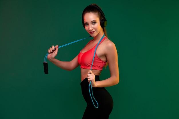 Attraente giovane donna in forma con corda per saltare e cuffie al chiuso fa esercizio