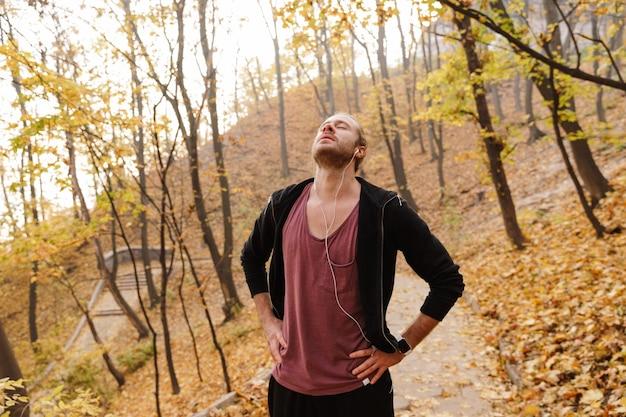 Attraente giovane sportivo in forma che fa jogging nella foresta autunnale, ascoltando musica con gli auricolari, riposando