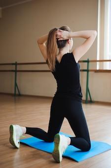 Ragazza attraente giovane modella fitness lavorando, facendo allenamento con i pesi. vista posteriore. viste del piede