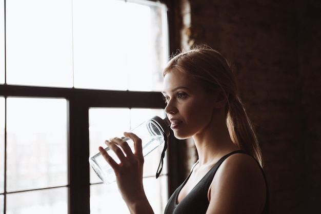 Acqua potabile della giovane donna attraente di forma fisica.