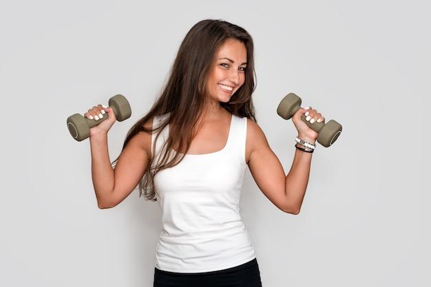 Attraente giovane donna fitness holding manubri, ragazza atletica facendo un allenamento fitness con manubri su sfondo grigio studio. Foto Premium