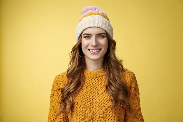 Attraente giovane ragazza in uscita dall'aspetto amichevole vestita caldo viaggio montagne sci divertirsi trascorrere le vacanze invernali famiglia delle alpi, sorridente ampiamente indossando cappello di velluto a coste maglione, sfondo giallo