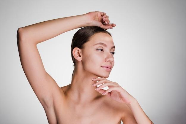 Ragazza attraente dopo la doccia, che mostra le sue ascelle senza capelli