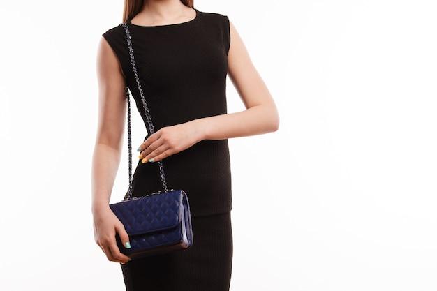 Attraente ragazza in abito nero in piedi con la borsa blu