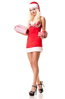 Attraente ragazza giovane vestita come ragazza di babbo natale che tiene una scatola con un regalo nelle sue mani in posa su uno sfondo bianco in studio