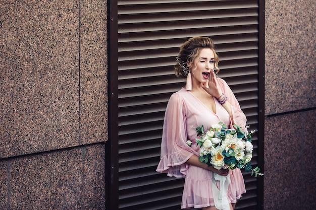 Giovane ragazza attraente in un abito corto con un mazzo di fiori in posa vicino al muro di granito con tapparelle.