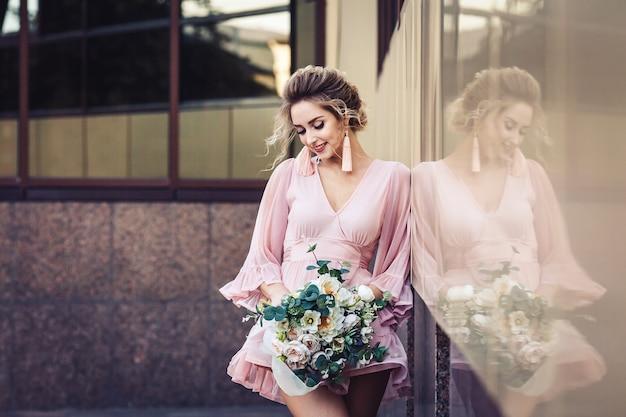 Giovane ragazza attraente in un abito corto con un bouquet di fiori in posa sulla strada vicino al muro dell'edificio.