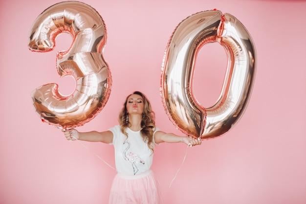 La ragazza attraente in vestiti dell'estate ha dato molto divertimento e celebra il suo compleanno, immagine isolata sulla parete rosa