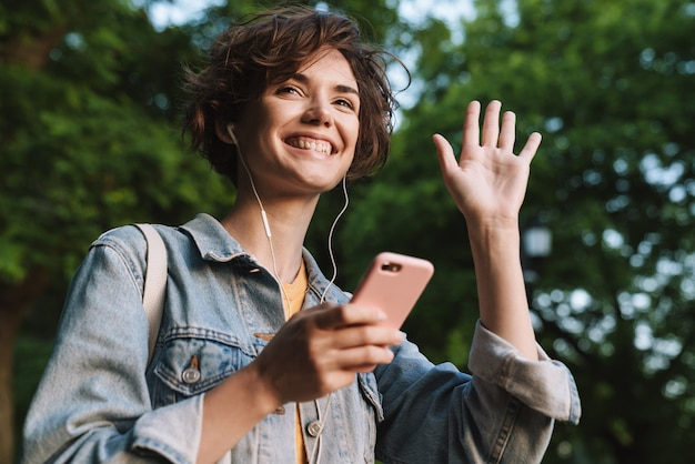 Attraente ragazza che indossa abiti casual trascorrono del tempo all'aperto al parco, ascoltando musica con gli auricolari, tenendo il telefono cellulare, agitando la mano