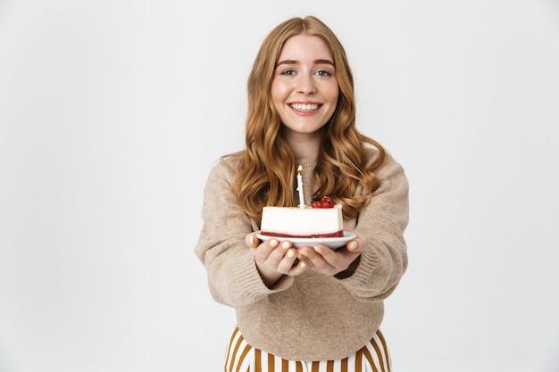Attraente ragazza che indossa un maglione in piedi isolato su un muro bianco, che mostra la torta di compleanno