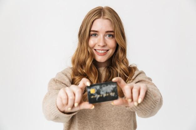 Attraente ragazza che indossa un maglione in piedi isolato su un muro bianco, mostrando una carta di credito in plastica