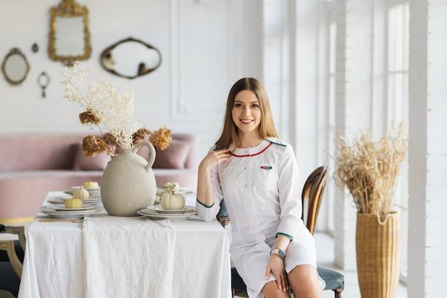 Giovane ragazza attraente in un camice medico bianco in un bellissimo salone di interni, clinica vip, bellezza e relax