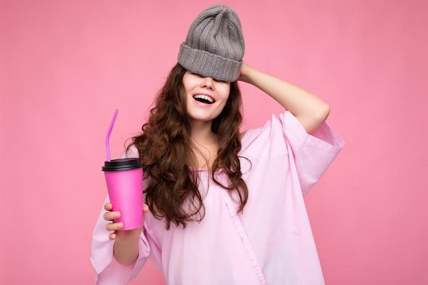 Attraente giovane donna bruna sorridente felice che indossa abiti alla moda di tutti i giorni isolati