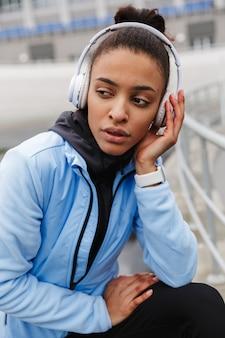Attraente giovane sportiva africana in buona salute che ascolta musica con gli auricolari wireless che si sforzano allo stadio