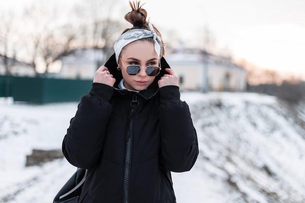 Attraente giovane donna hipster in eleganti occhiali da sole neri in giacca invernale alla moda nera con uno zaino in pelle con una bandana cammina in una giornata invernale e godersi il fine settimana.
