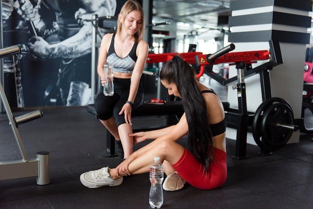 Attraenti giovani donne in tenuta sportiva sedute sul pavimento e bevendo acqua dopo un duro allenamento in palestra